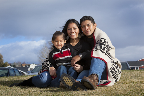 Photo of Native family wrapped in a blanket