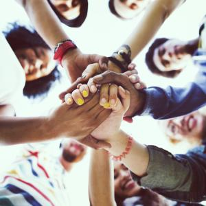 A photo of a group of people all holding hands in a circle
