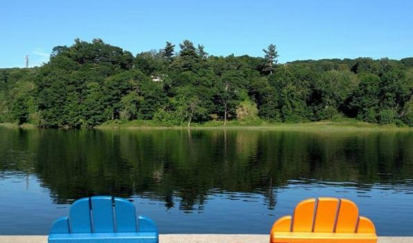 Two adirondack chairs on deck look out at a lake