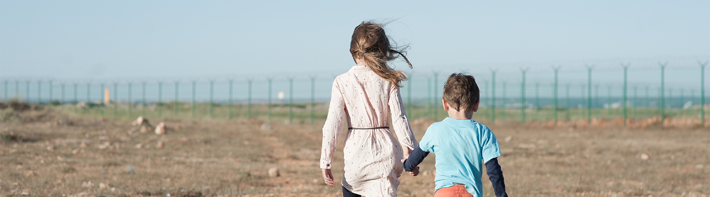 Two kids holding hands walking towards a fence